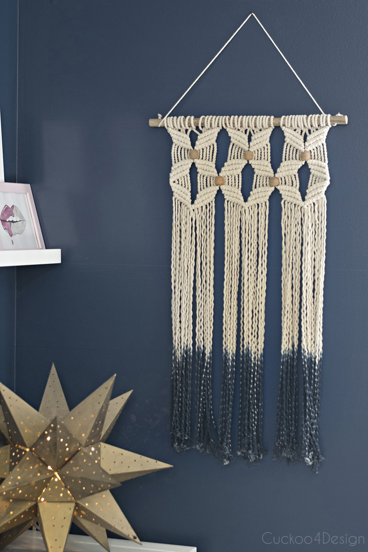 macrame wall hanging on dark blue walls