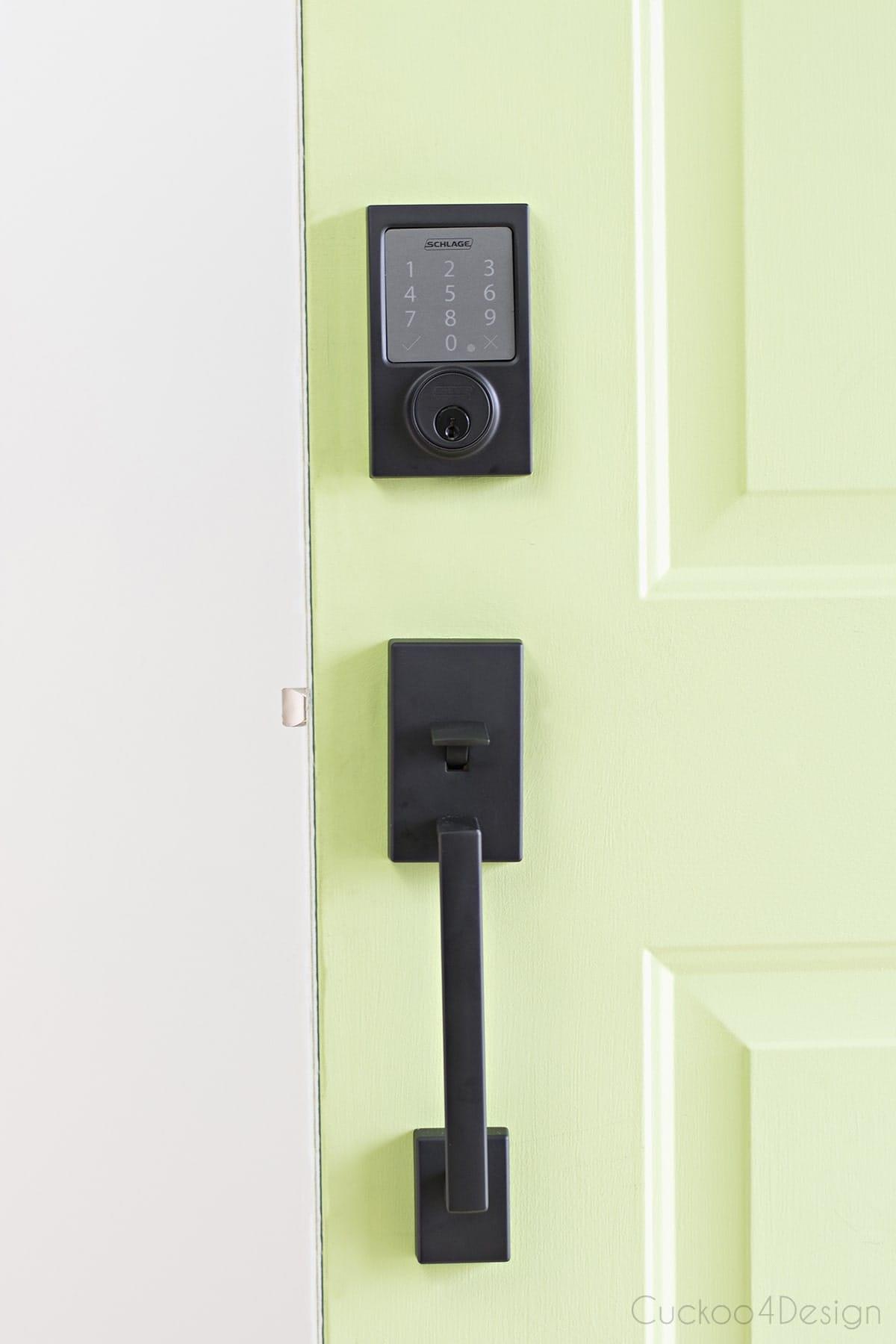 matte black The Schlage Sense™ Smart Deadbolt on a lime green front door