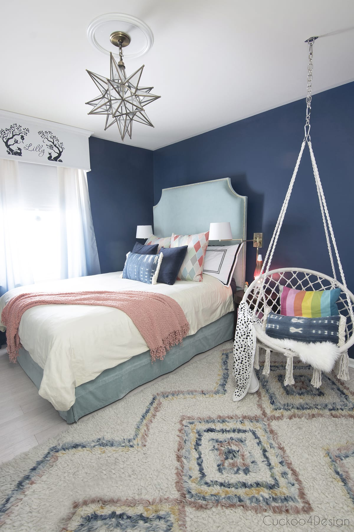 dark blue girls bedroom with turquoise DIY fabric headboard, hanging chair and colorful moroccan rug
