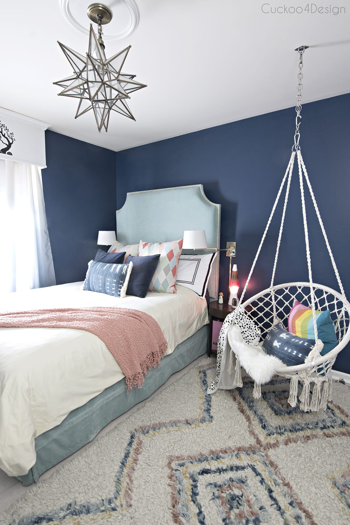 dark blue girls room with turquoise velvet bed, macrame hanging chair and colorful Moroccan shag rug