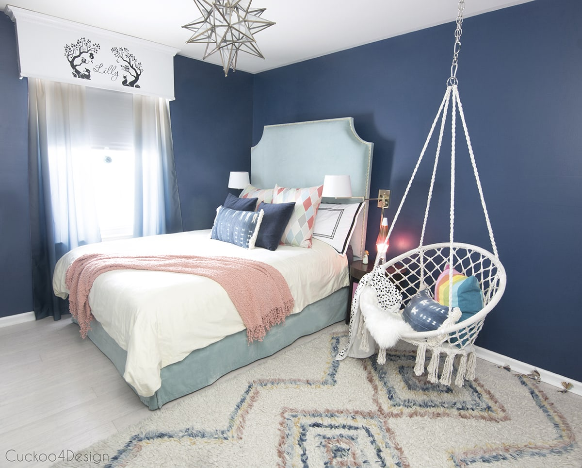 dark blue girls room with macrame hanging chair and colorful Moroccan shag rug