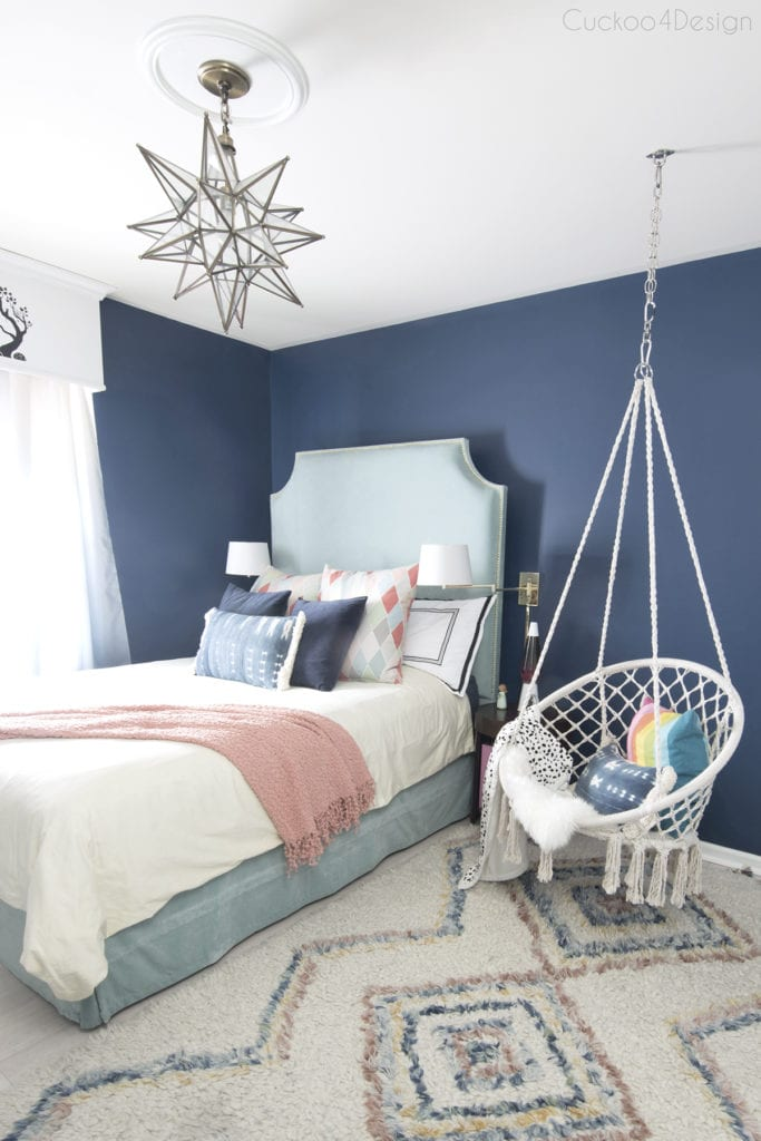 dark blue girls bedroom with turquoise velvet bed , macrame chair and moroccan shag rug