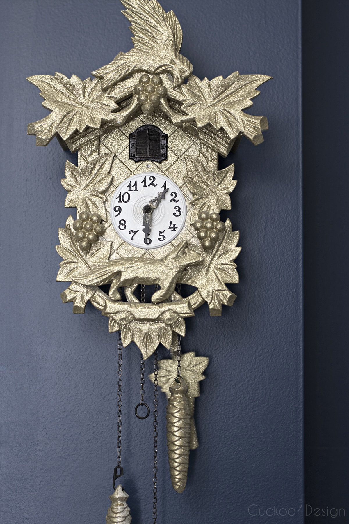 gold sparkly cuckoo clock on dark blue walls