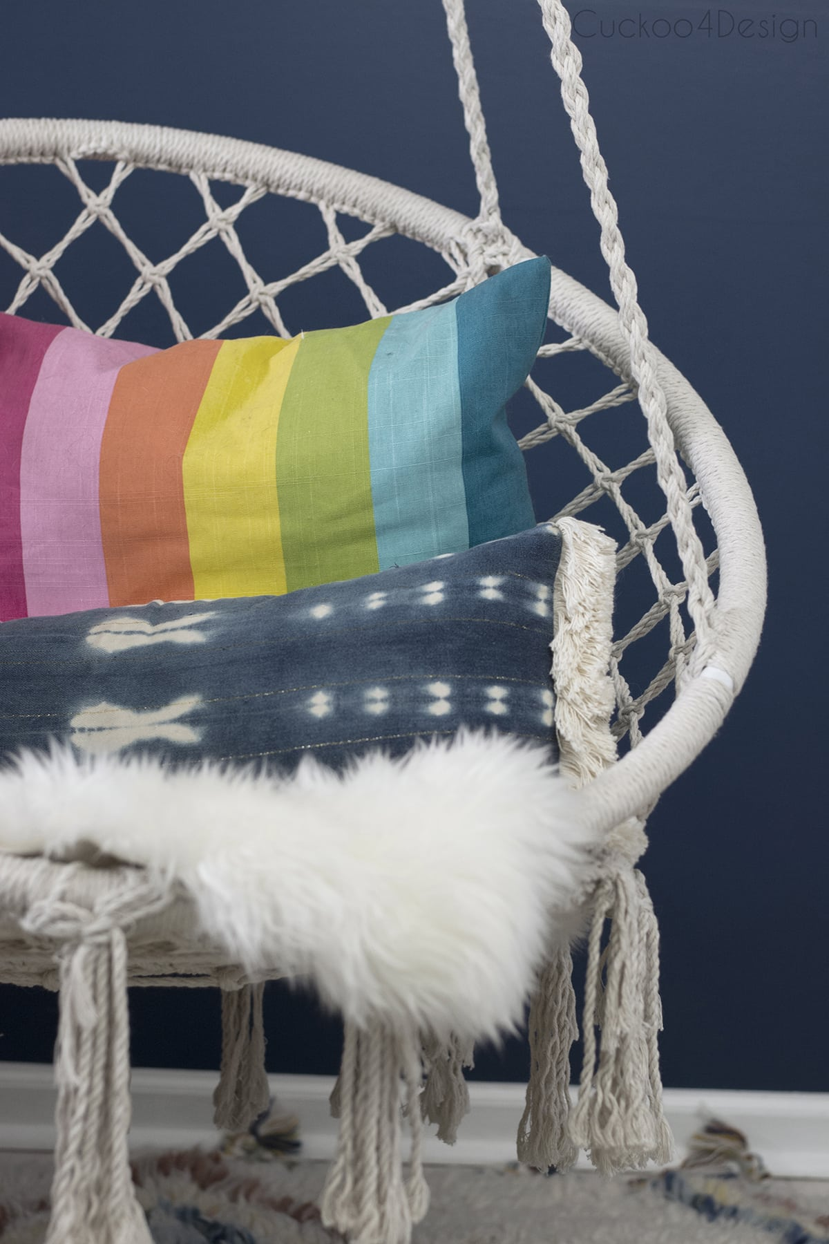 rainbow pillow and mudcloth pillow in macrame hanging chair