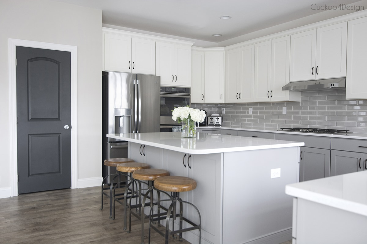 dark grey interior doors in kitchen with white upper cabinets and light grey bottom cabinets