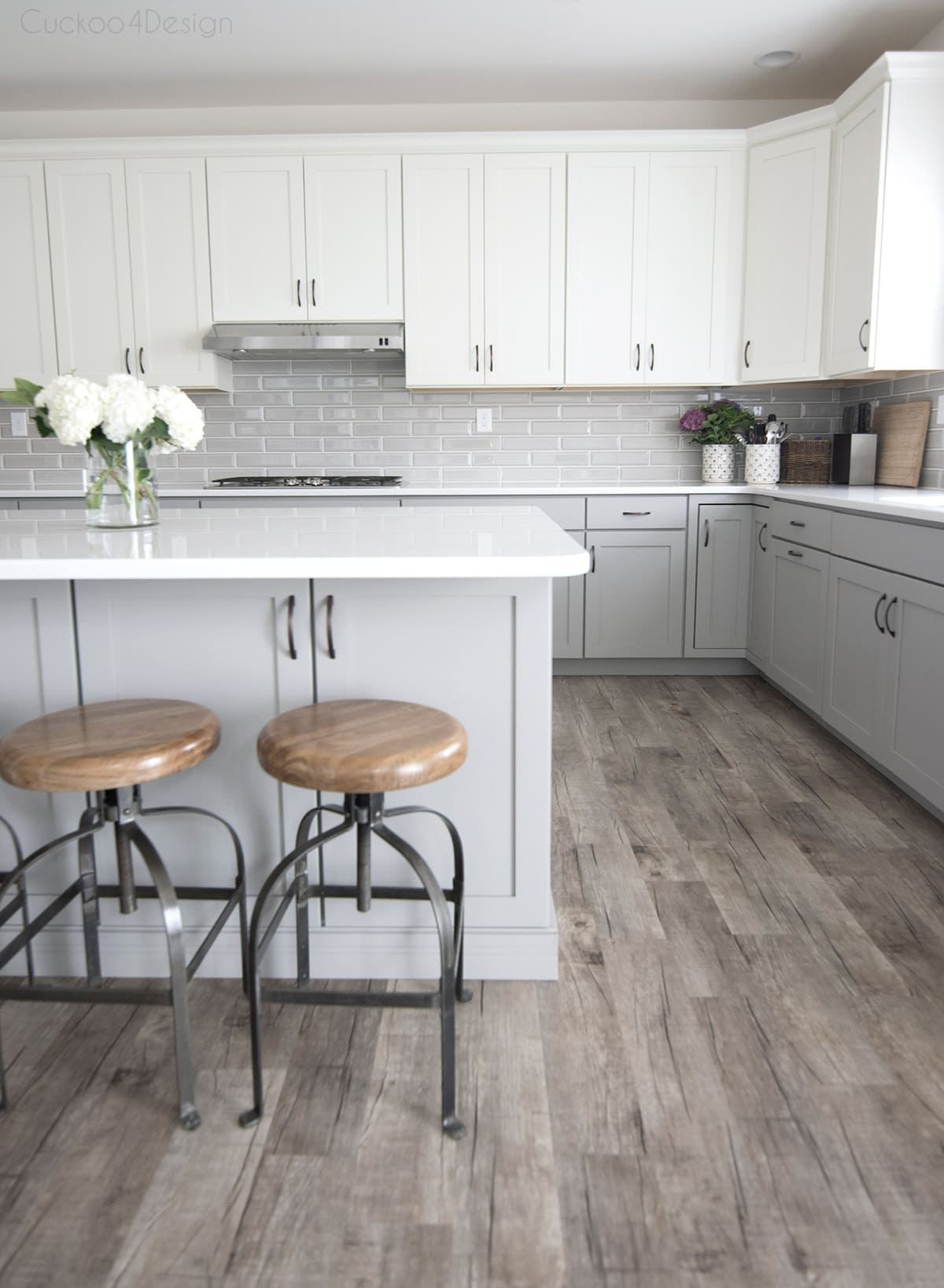 beautiful light grey kitchen cabinets with white upper cabinets and white quartz countertops