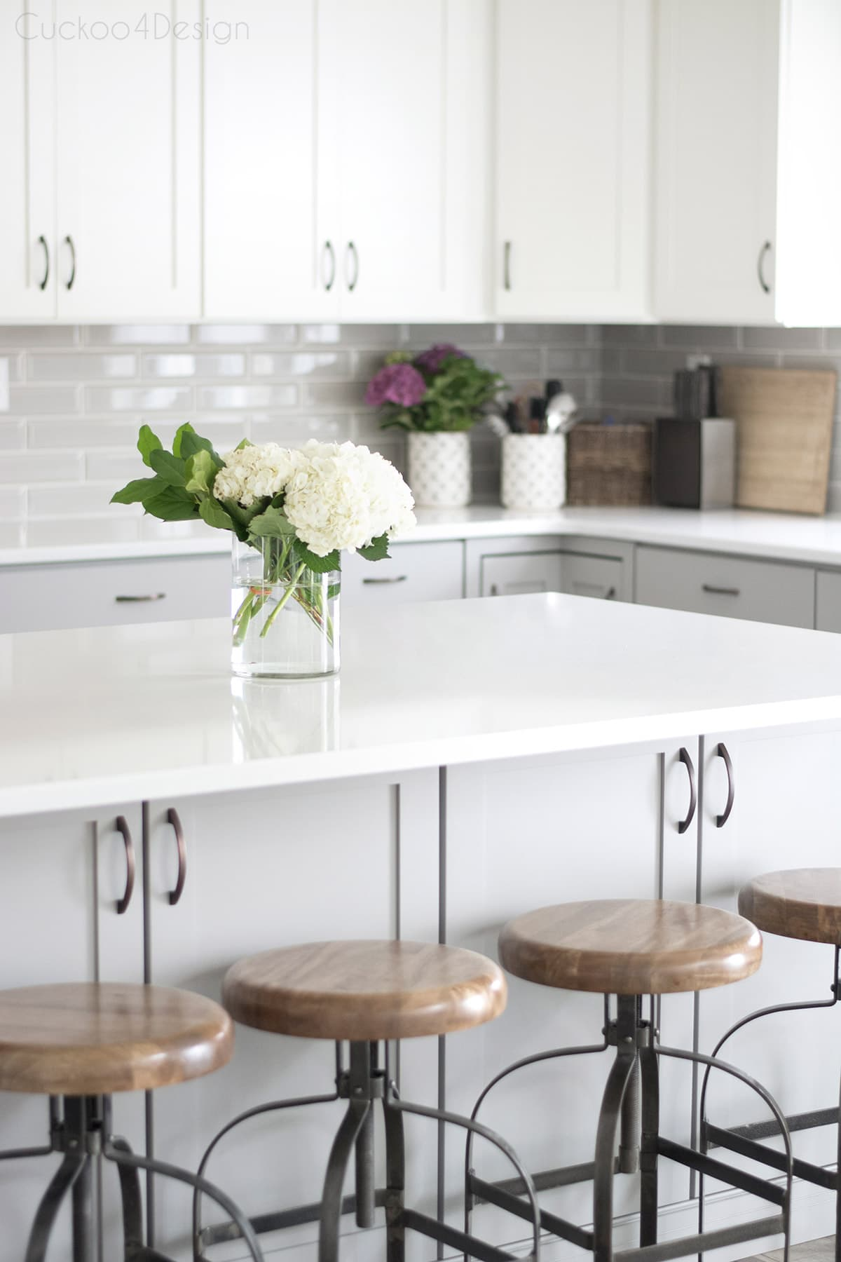 beautiful grey kitchen island with white quartz countertop and metal and wood counter stools