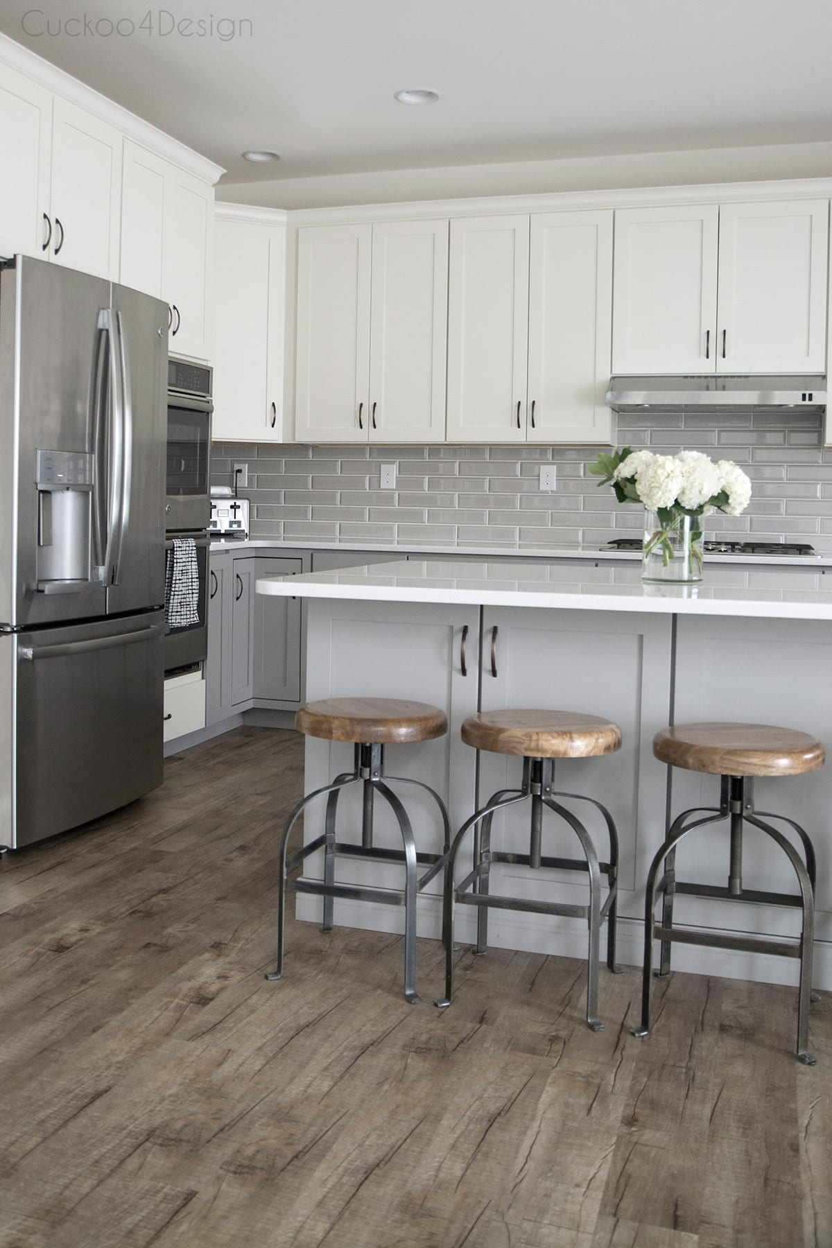 vinyl plank flooring and wood and metal counter stools in grey and white kitchen