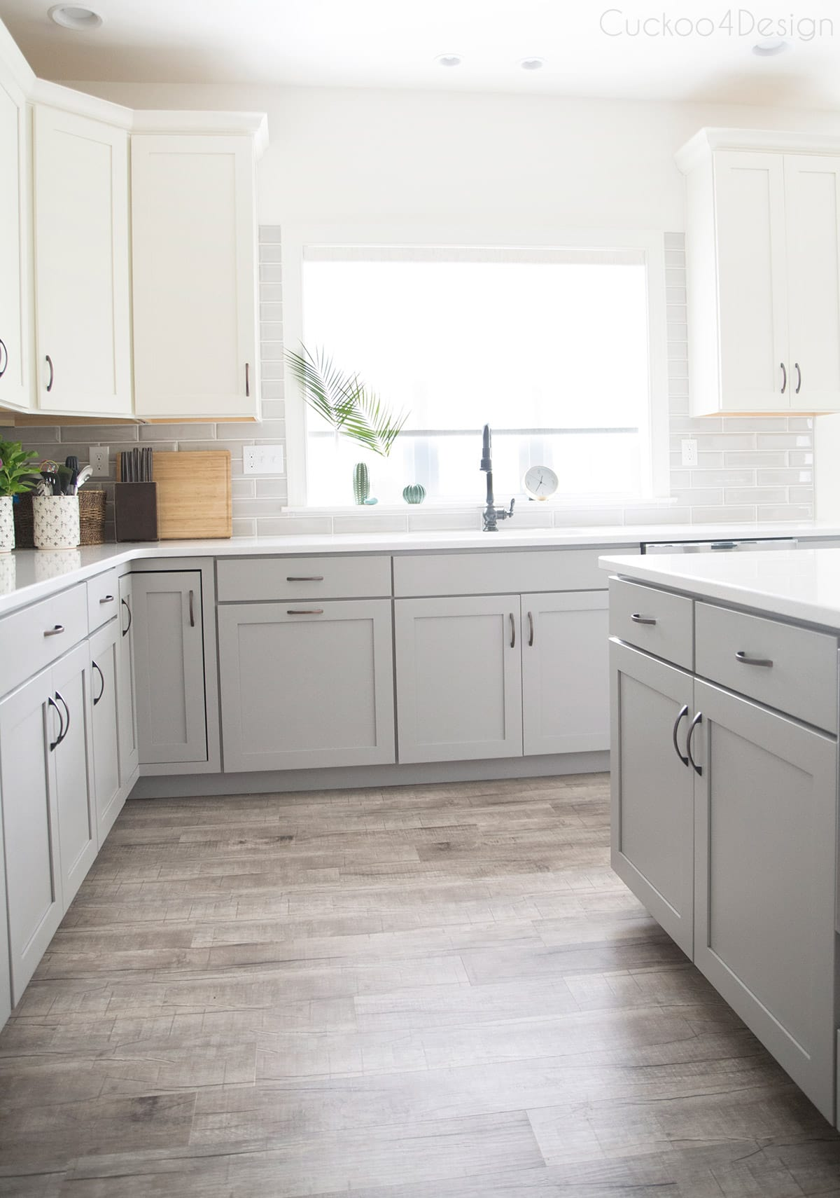 glossy grey subway tiles in white and gray kitchen with vinyl plank flooring