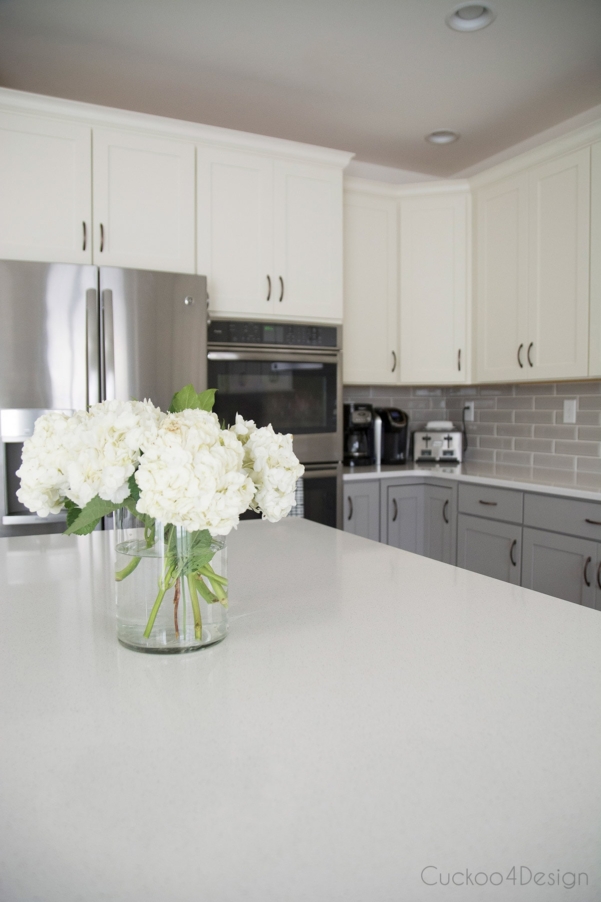 flowers on kitchen island with grey and white cabinets