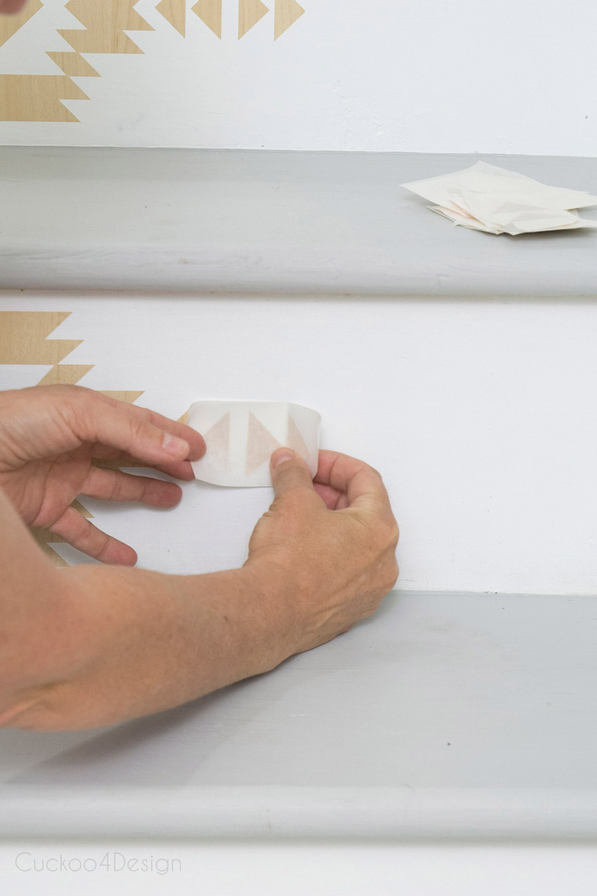 placing self-adhesive vinyl stair riser decals on painted surface