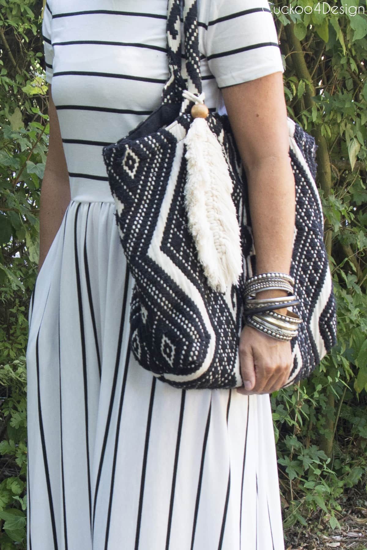 beaded macrame feather purse charm on black and white shoulder bag