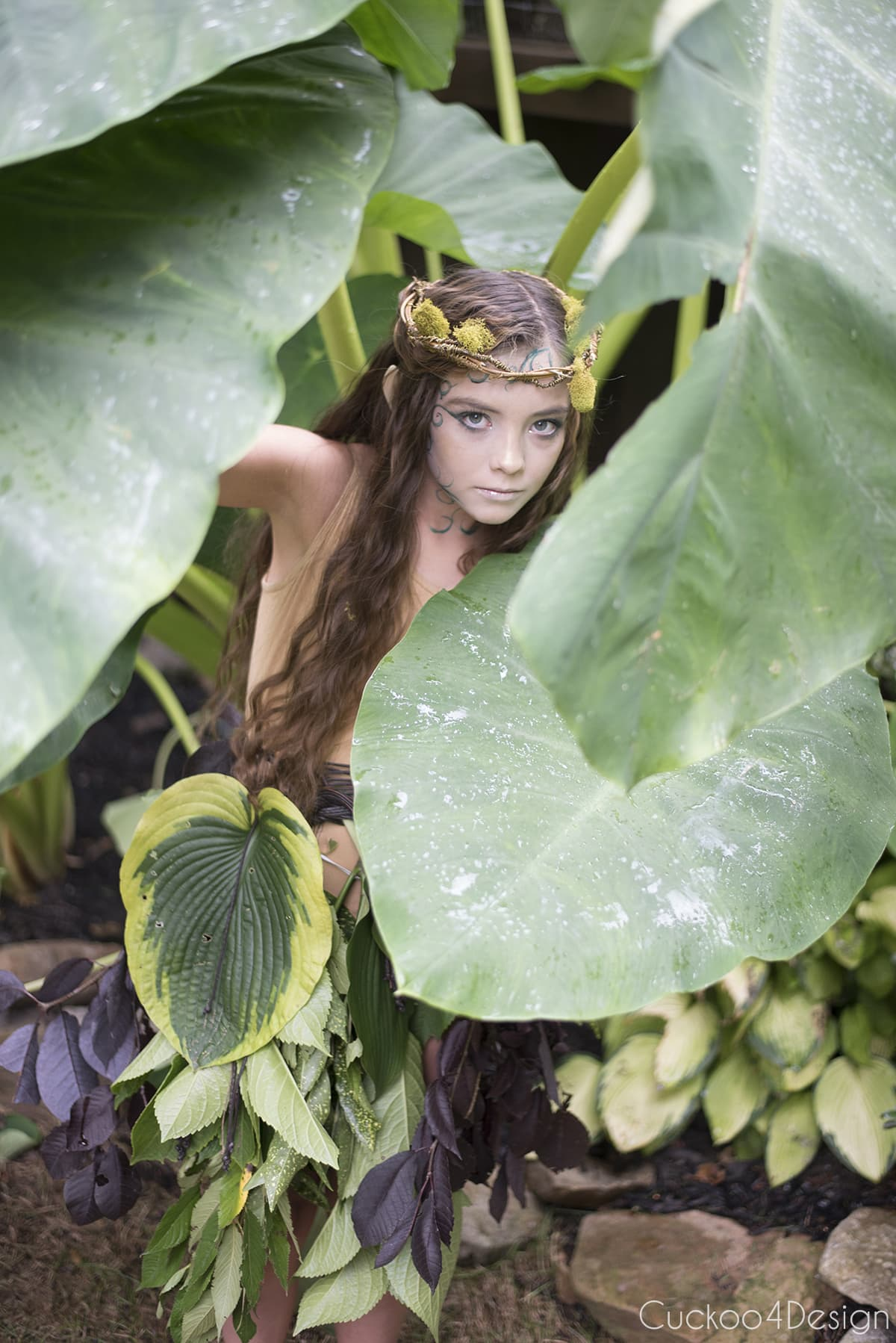tiny forest elf hiding under big leaves