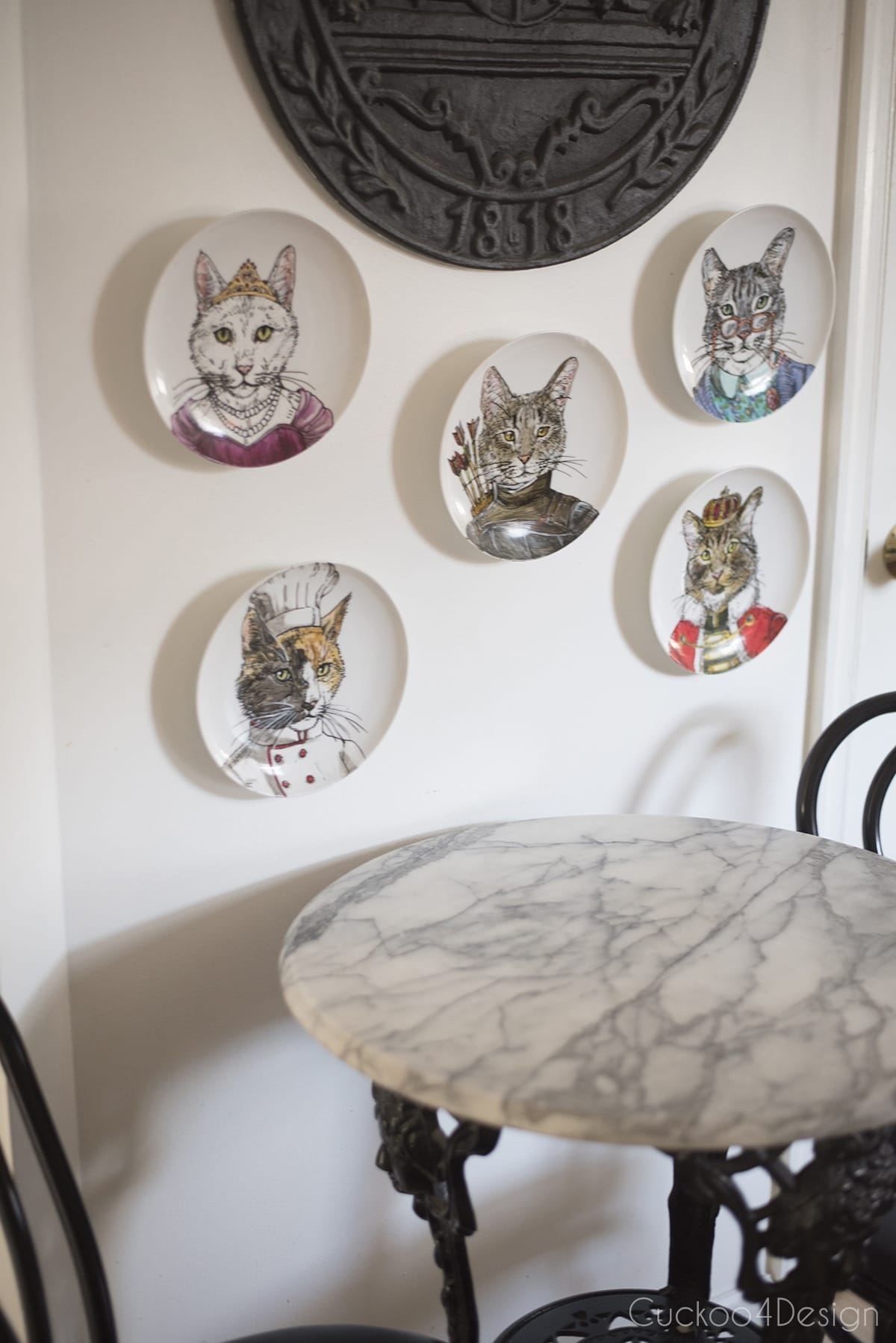 decorative animal plates above our vintage wrought iron and marble bistro table