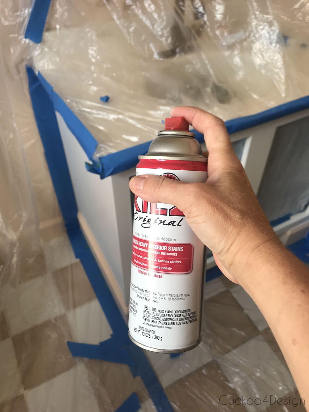 spray painting vanity in room for budget bathroom remodel