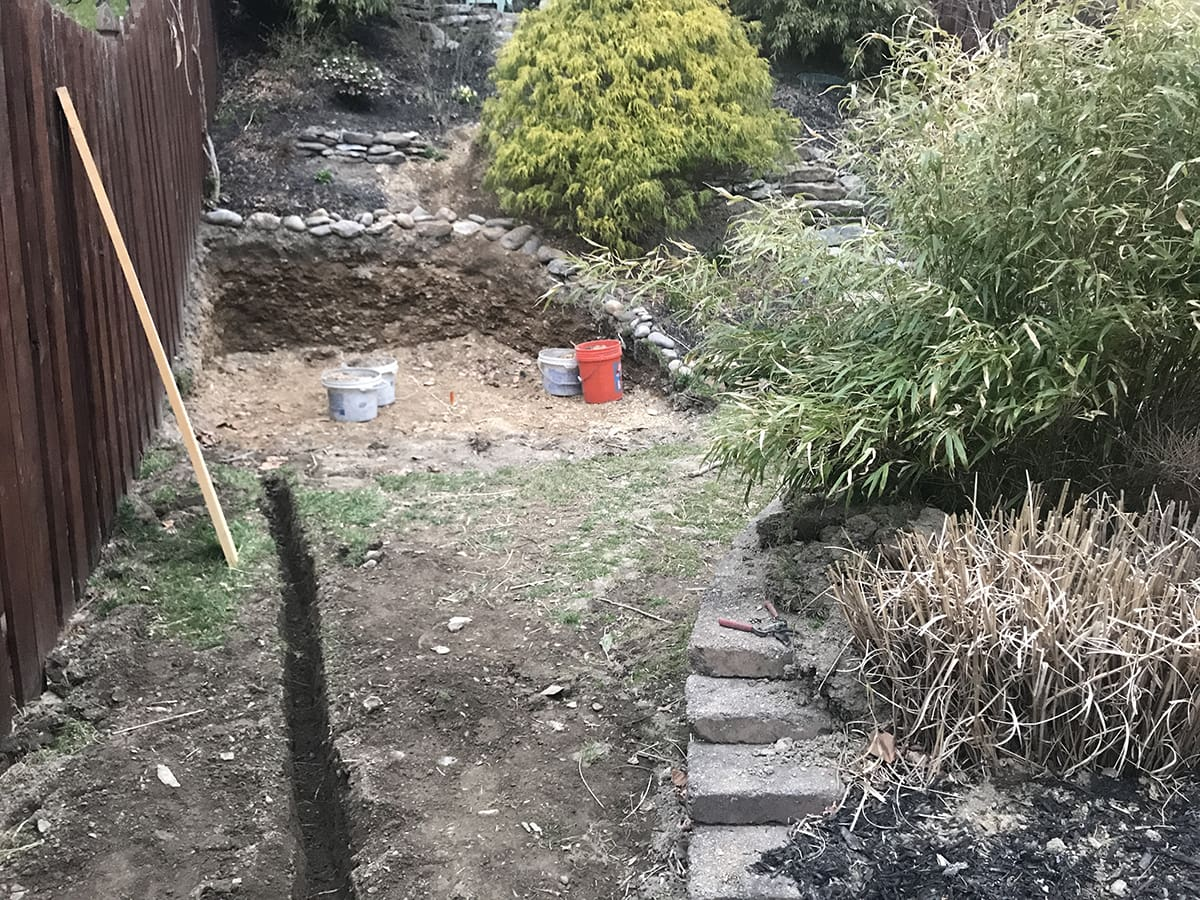digging into a hill for a stock tank pool