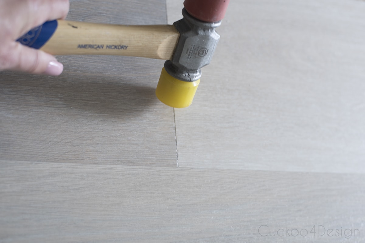 tapping vinyl wood plank flooring planks in place with a rubber mallet