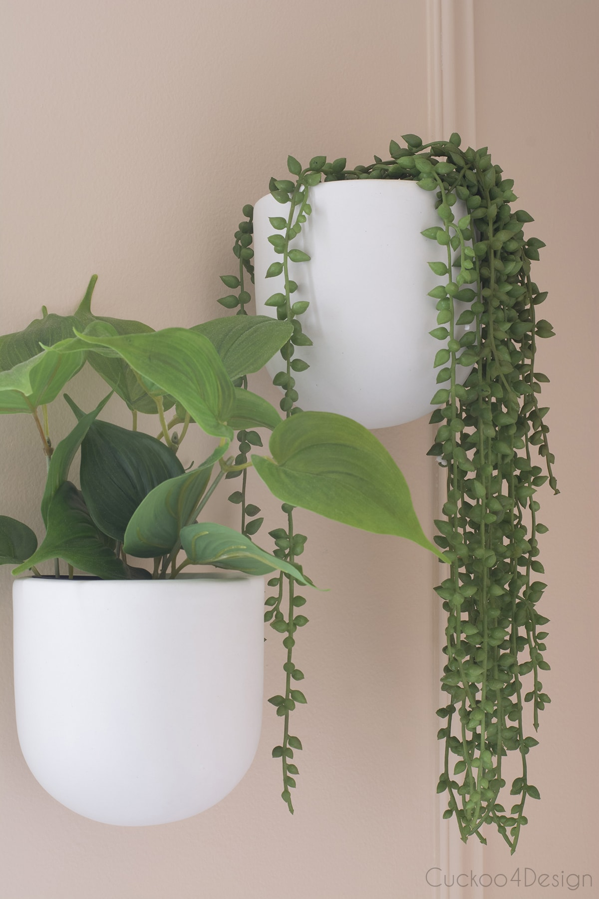 hanging wall planters with faux plants in blush budget bathroom remodel