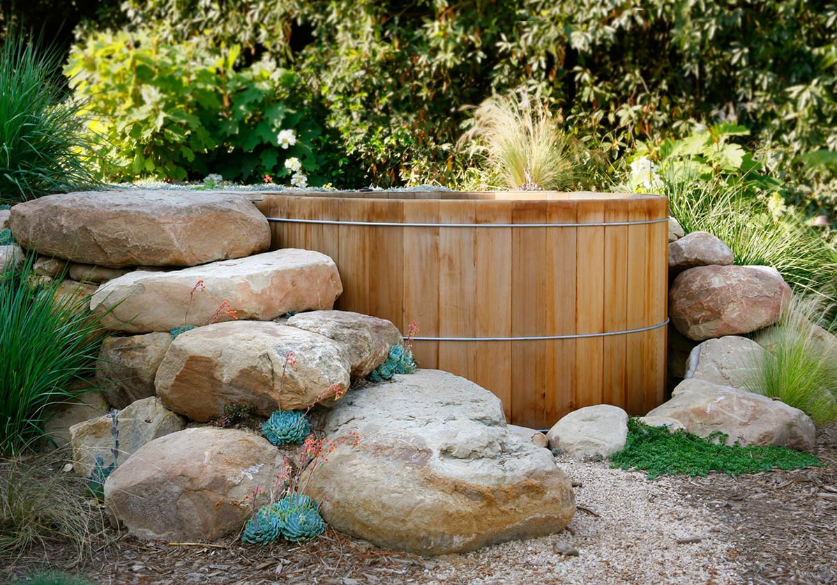 wooden stock tank pool with rock surround