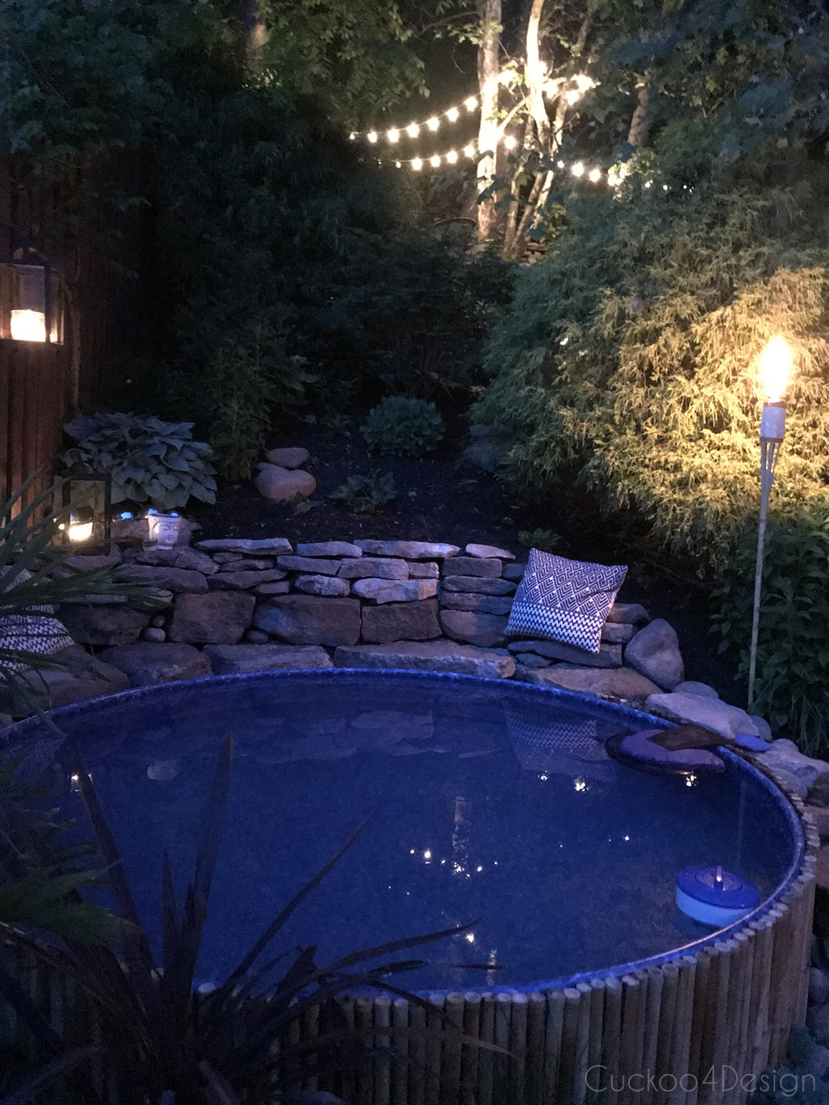 stock tank pool with tiki torches at night