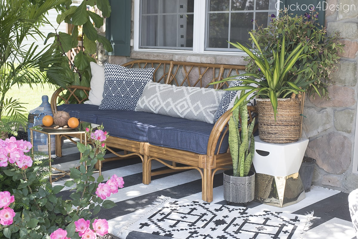 rattan sofa on porch with blue cushions