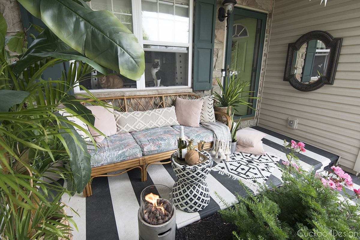 black and white striped porch with 70s rattan sofa