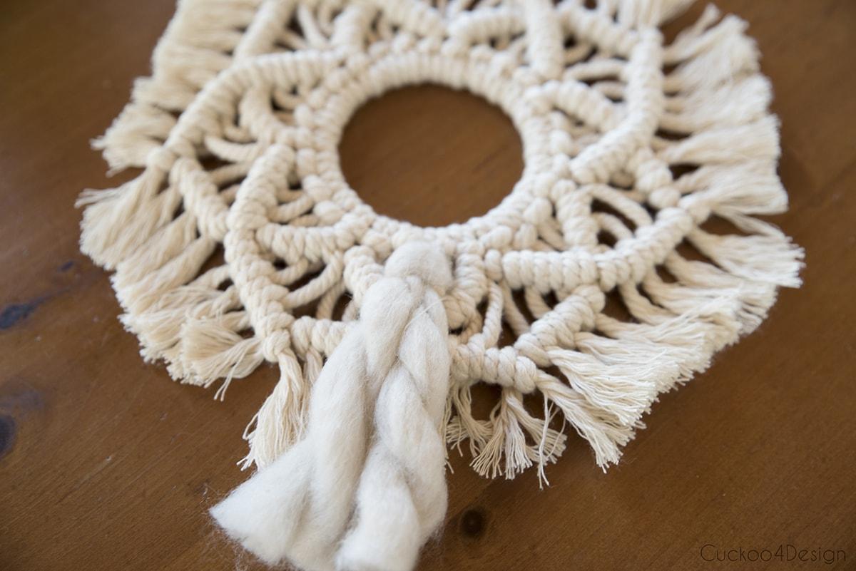 weaving thick wool through macrame wreath