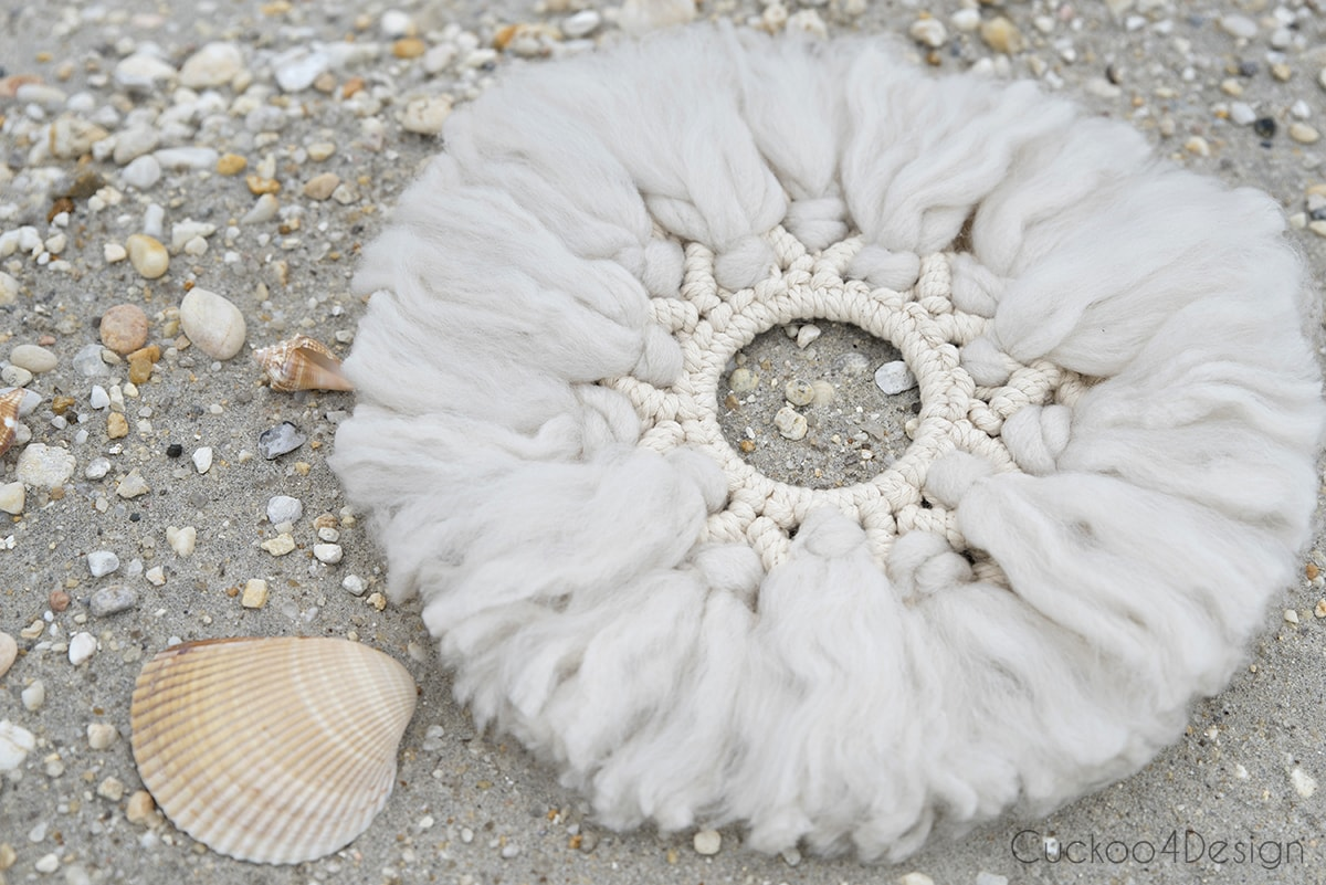 wool and yarn macrame wreath on beach sand