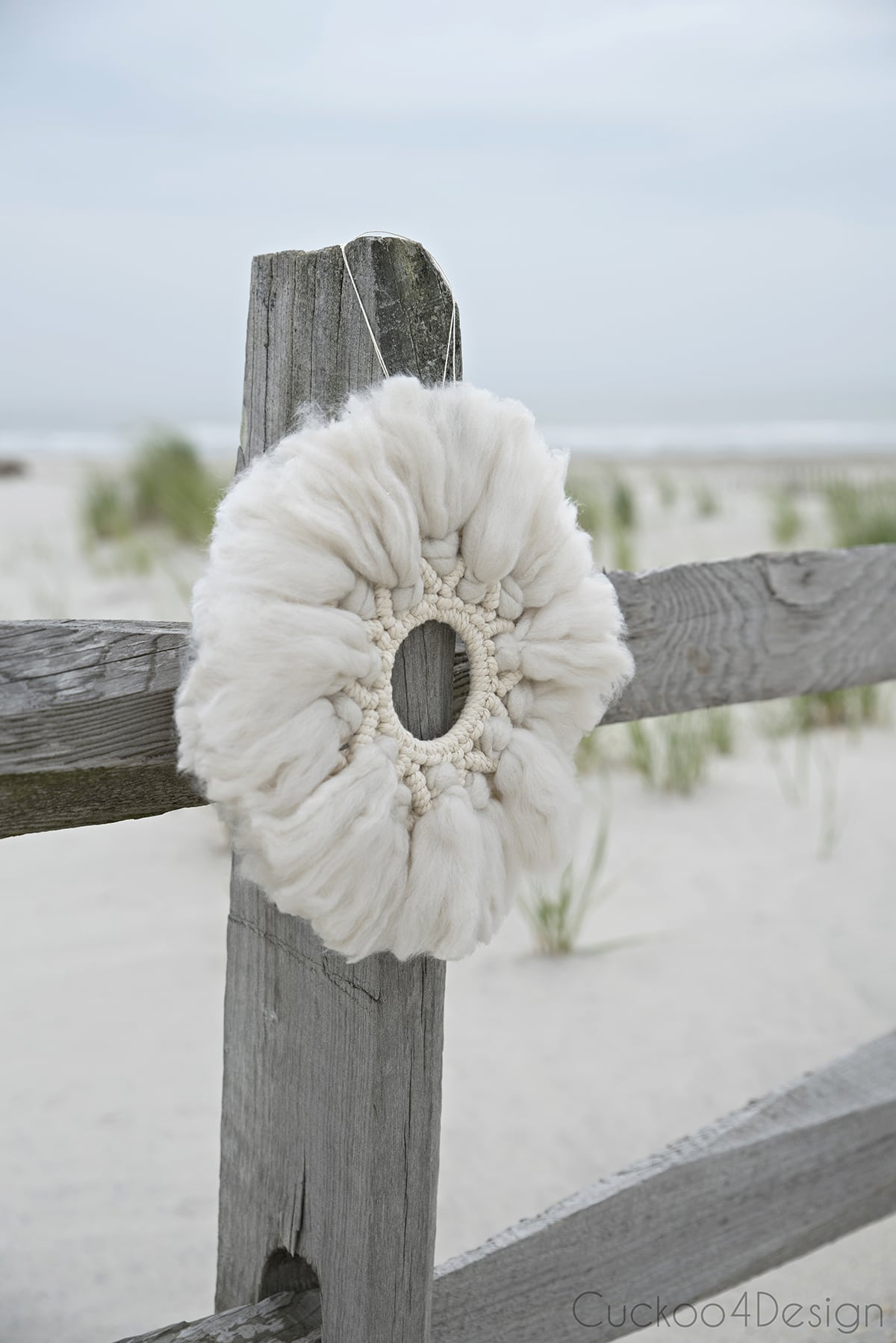 wool and yarn macrame wreath hanging on beach fence