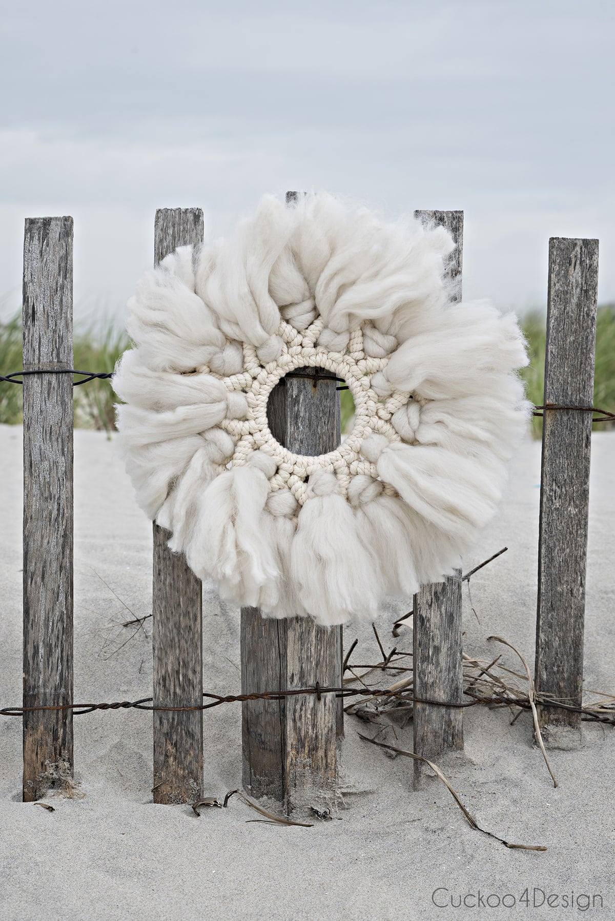 wool and yarn macrame wreath hanging on beach dunes fencing