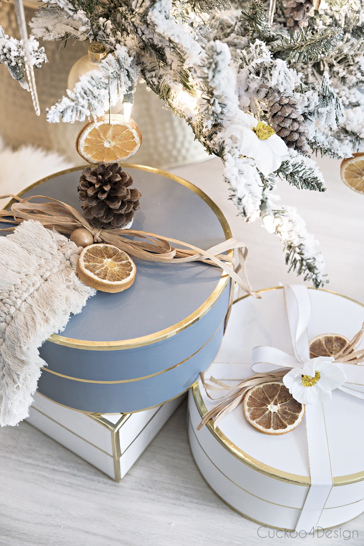 blue, white and gold presents wrapped under flocked natural German Christmas tree