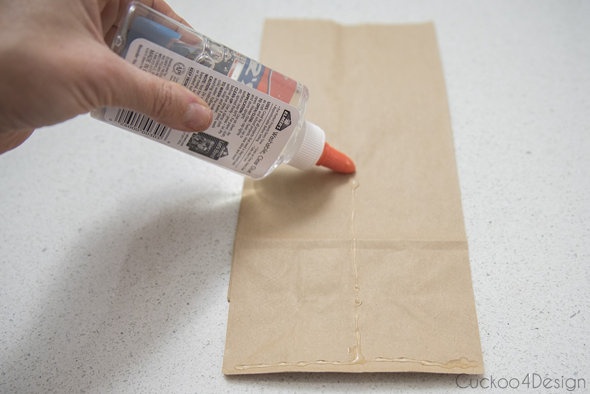 gluing lunch bags together to turn them into 3D paper snowflakes