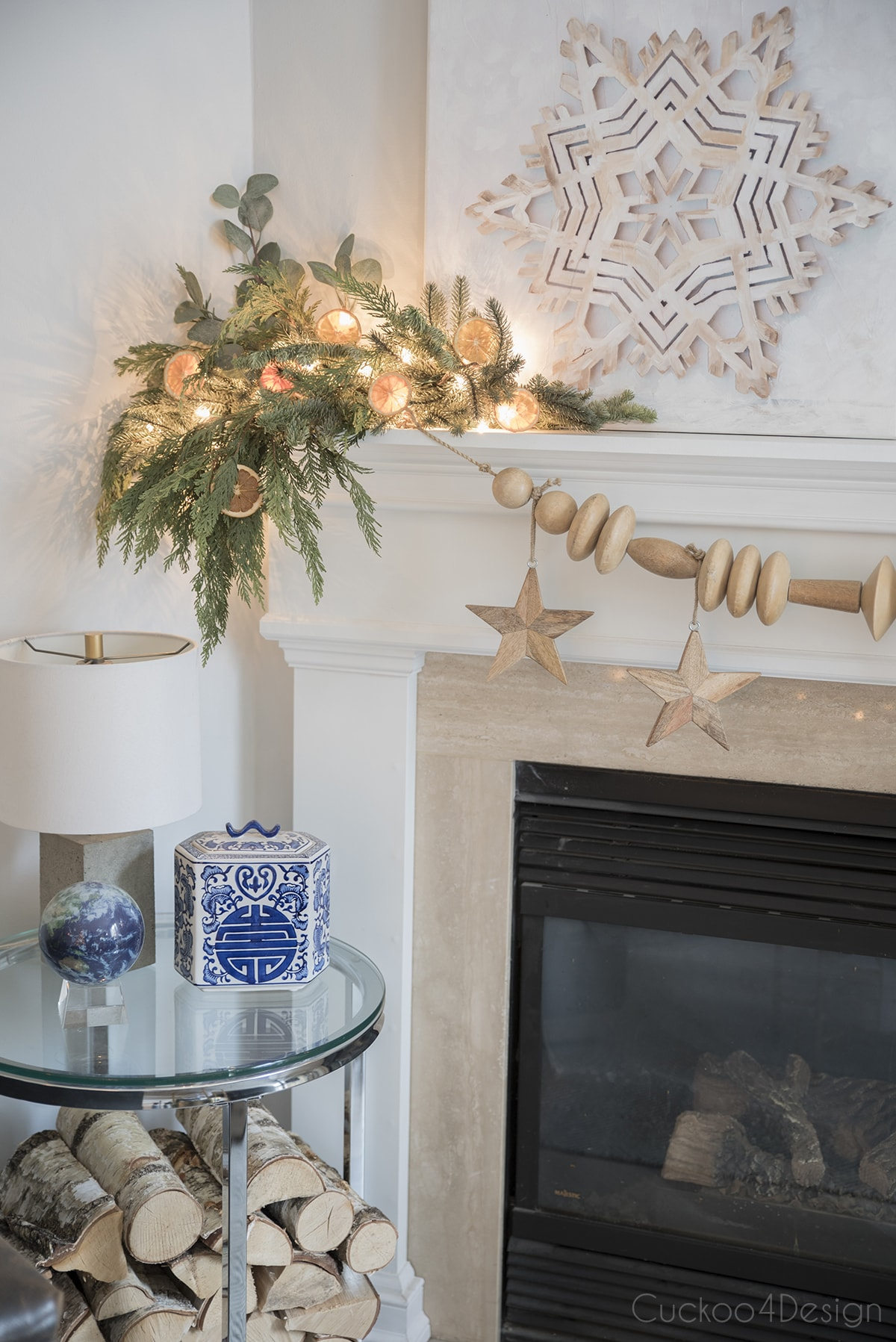 fireplace with snowflake art and birch wood pile