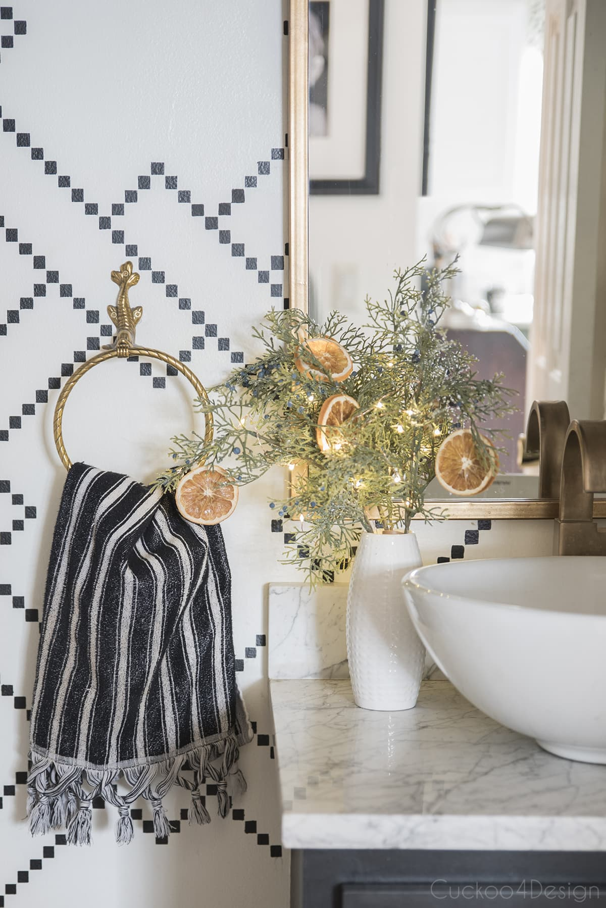 Christmas flower arrangement with cedar, dried oranges and fairy lights in powder room
