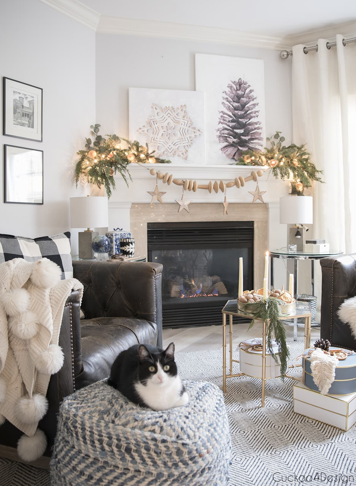 fireplace with wooded garland, DIY canvas art and leather swivel chairs