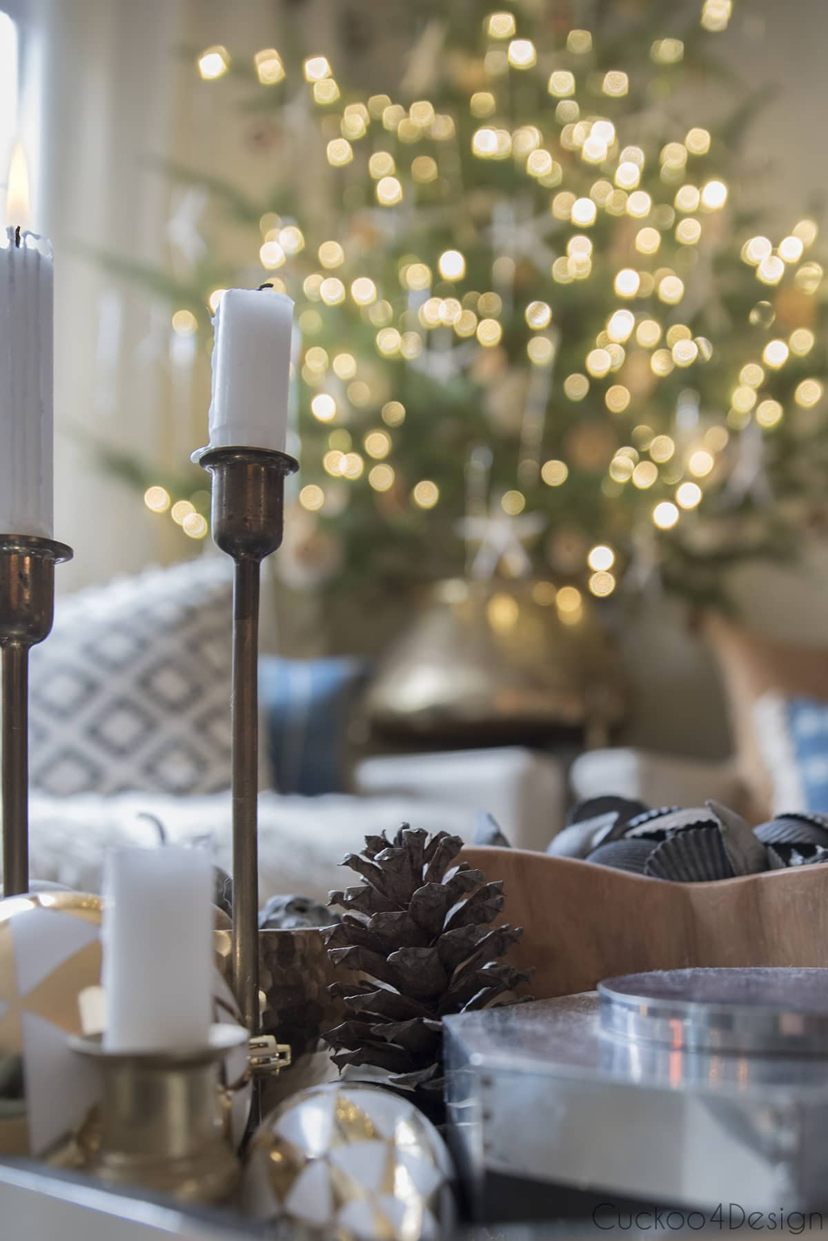 lit candle in front of live tabletop Christmas tree