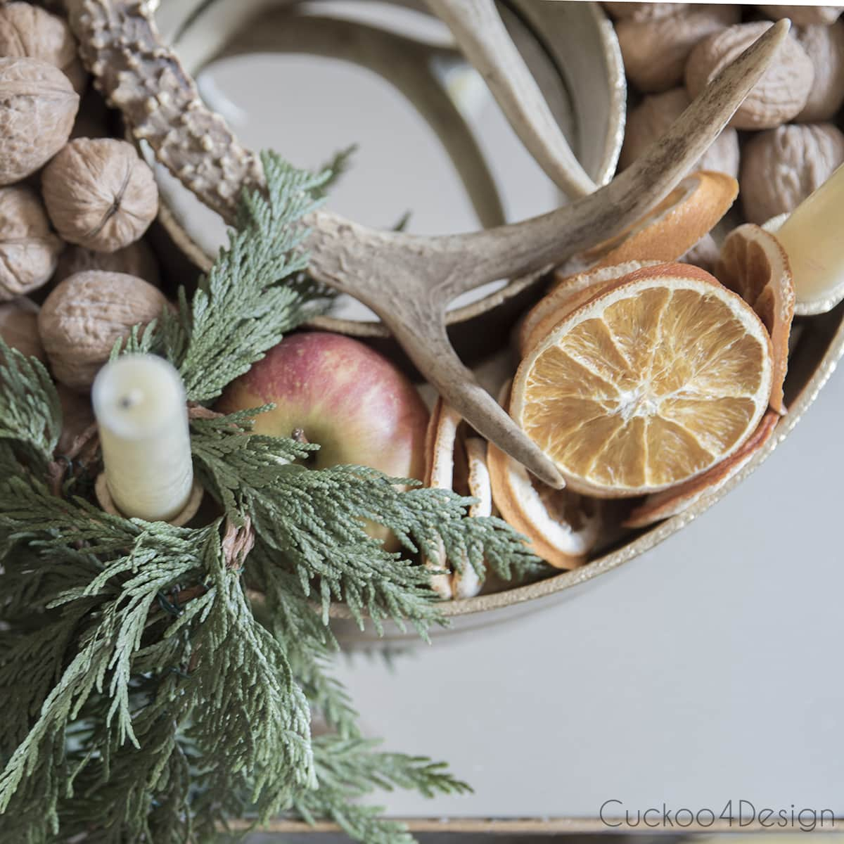 advent wreath on gold tray with nuts, dried oranges, apples, cedar and antlers