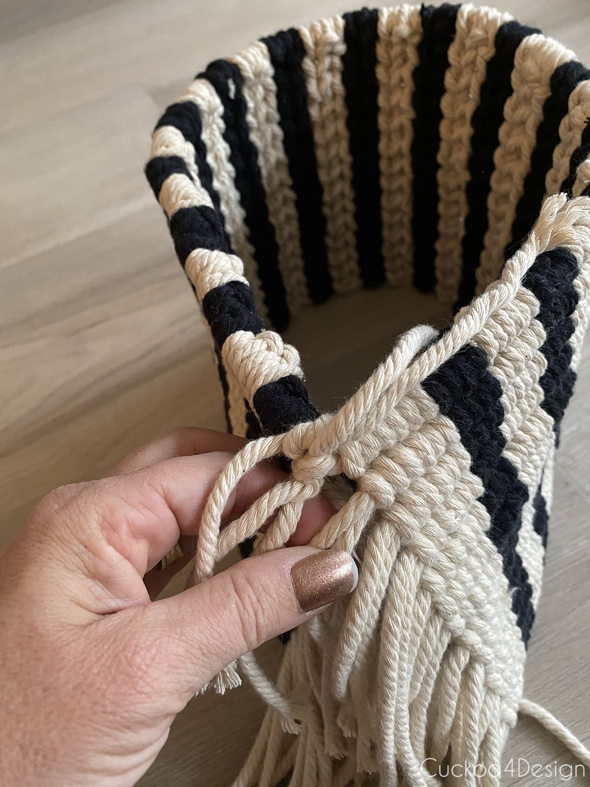 tying the macrame yarn ends to form a planter