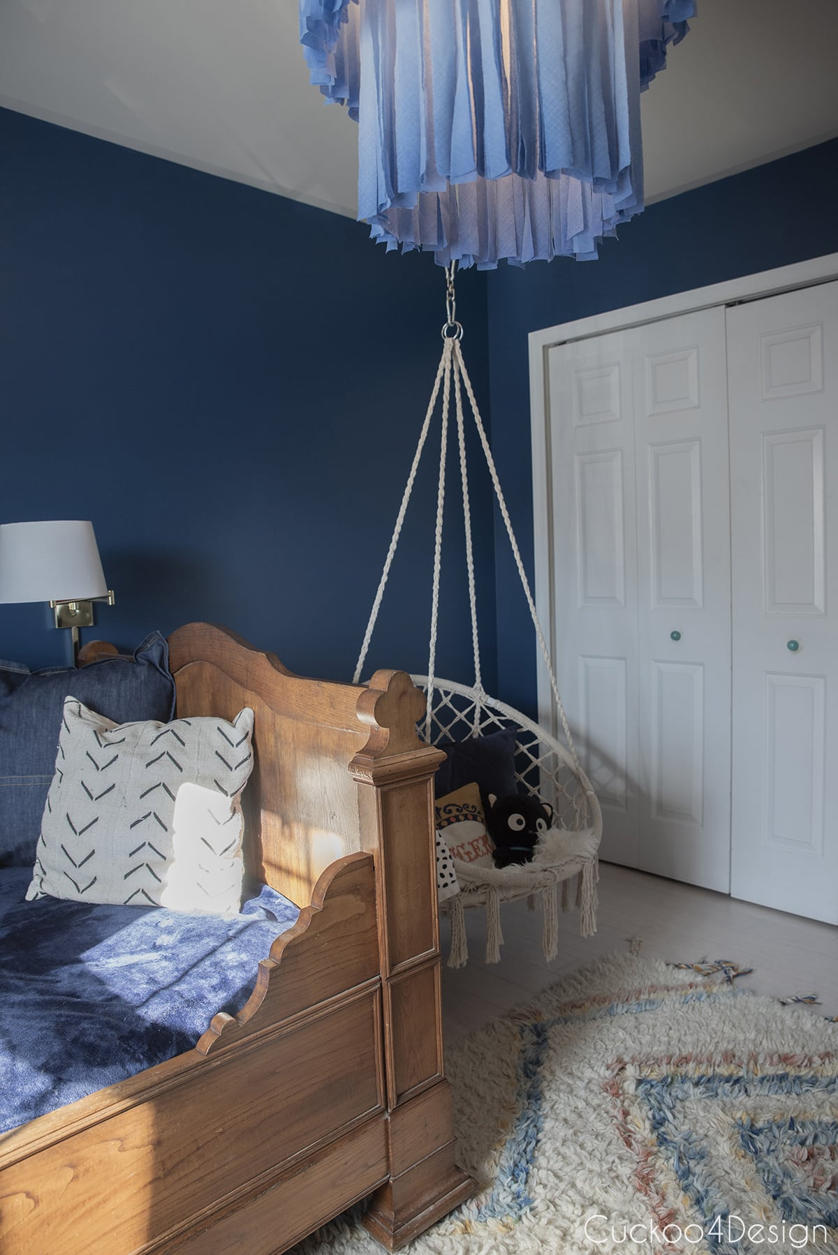 French antique bed in dark blue girls room
