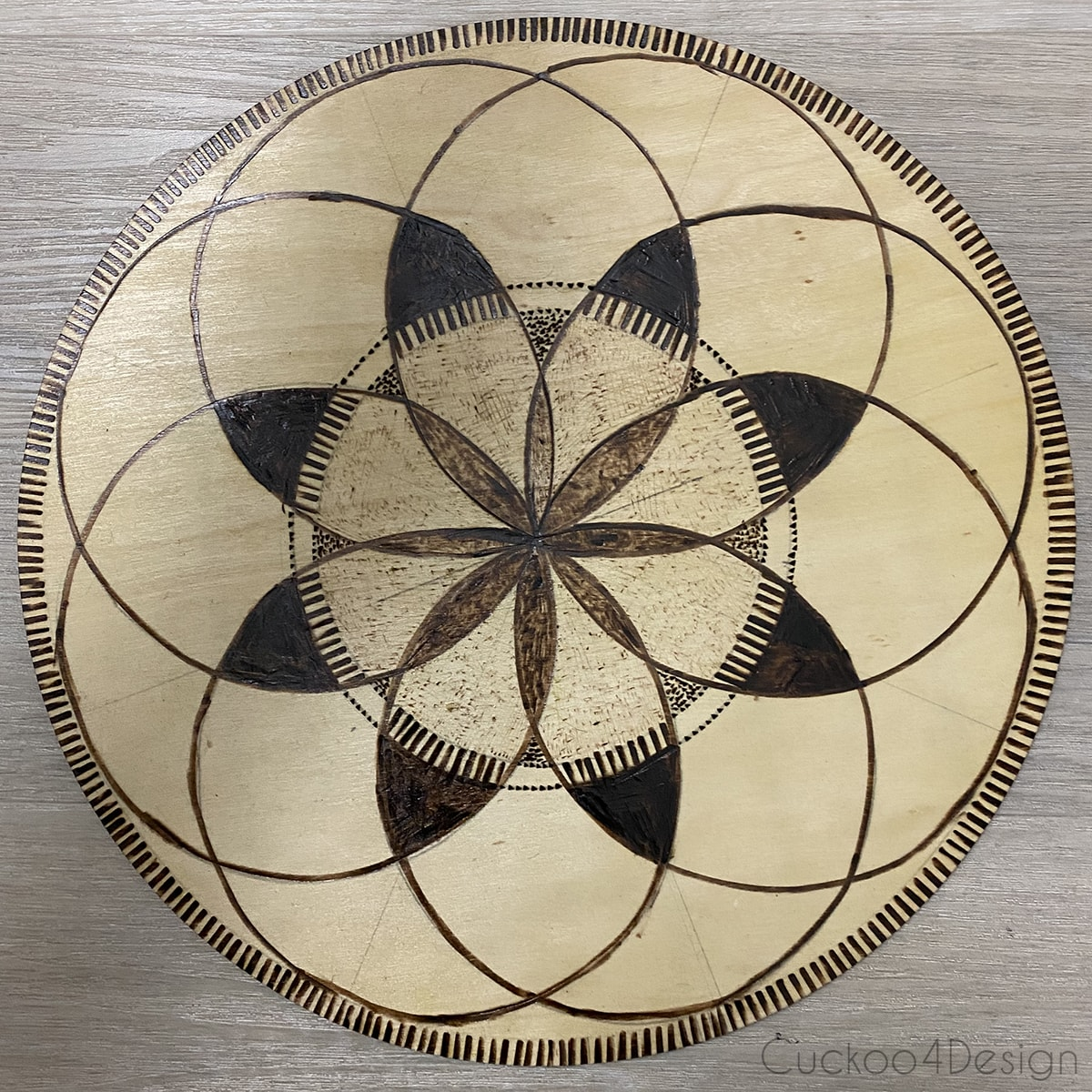 Wood burned circular geometric wall art piece without color