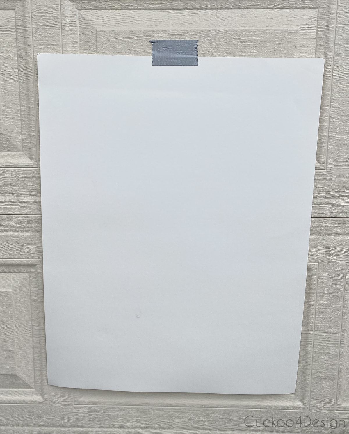 hanging poster board on outdoor wall with tape