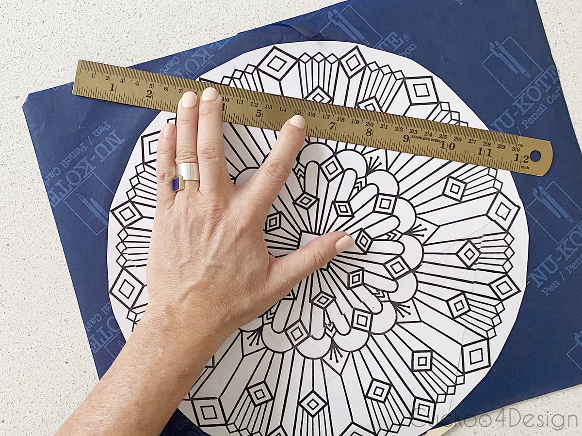 using a ruler and pencil to trace the pattern