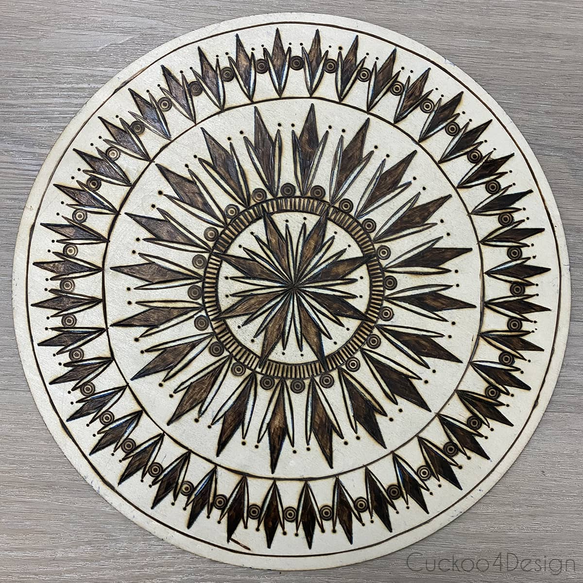 structure mandala with straight lines and dark wood burned shapes