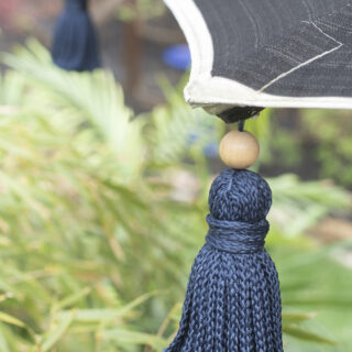 closeup of tassels attached to umbrella with safety pin