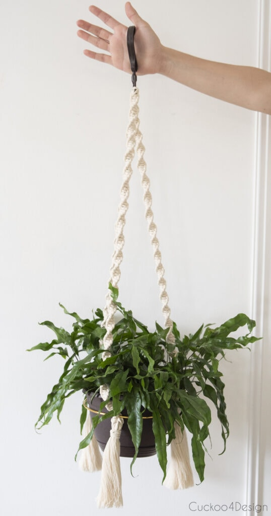 arm holding finished macrame hanging planter to show full length