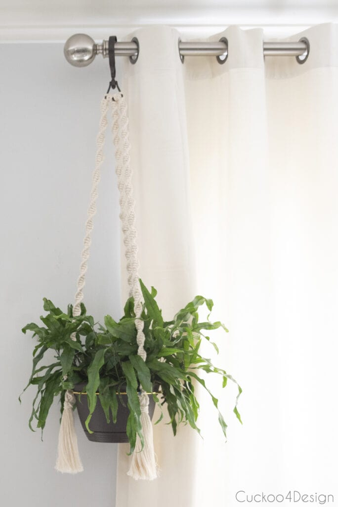 finished macrame planter hanging on curtain rod