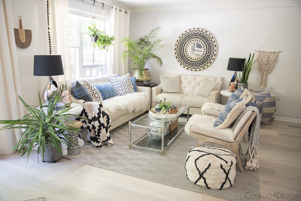 entire room view of living room with multiple plants, black and white accessories and blue accents