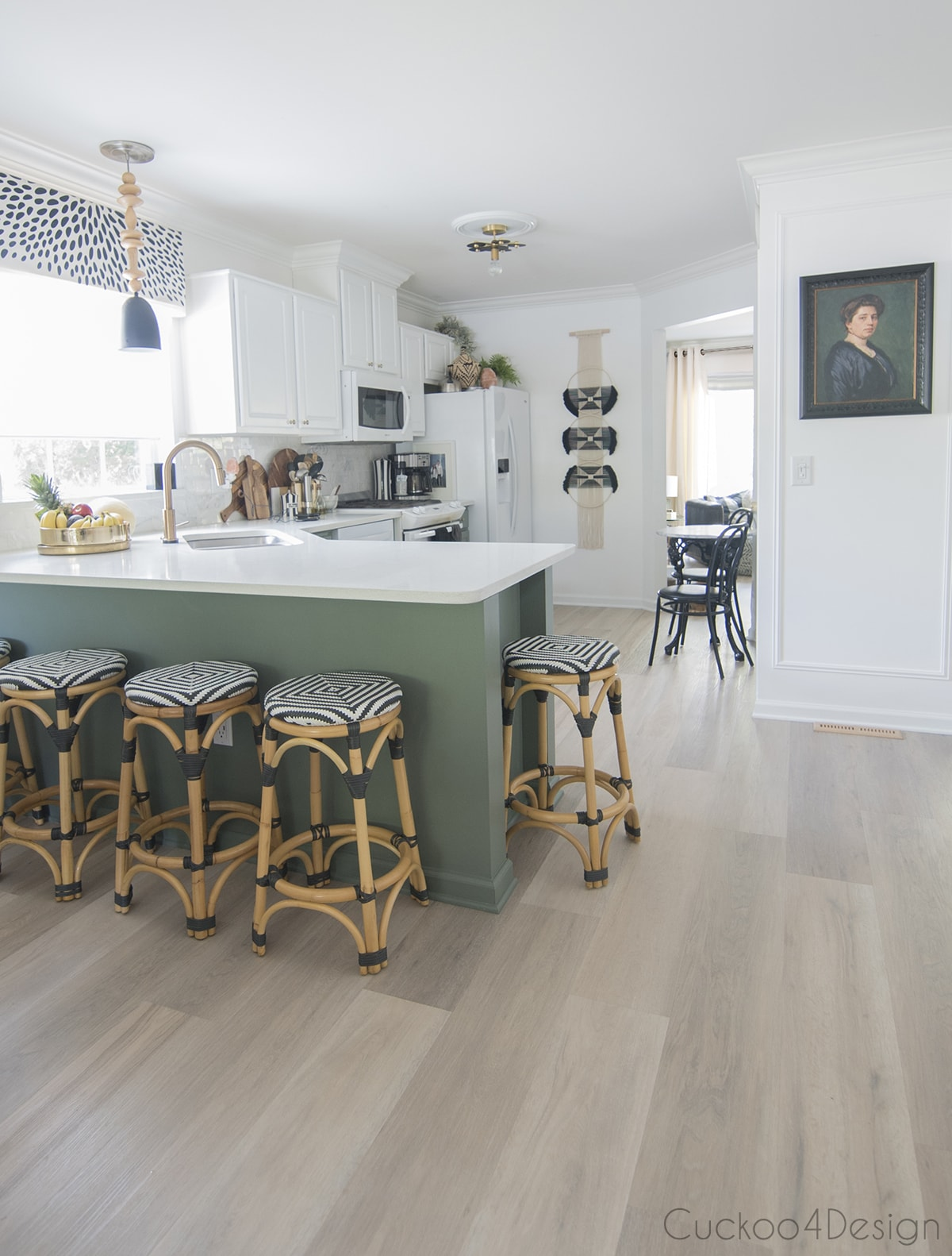 green and white kitchen with light vinyl plank wood flooring