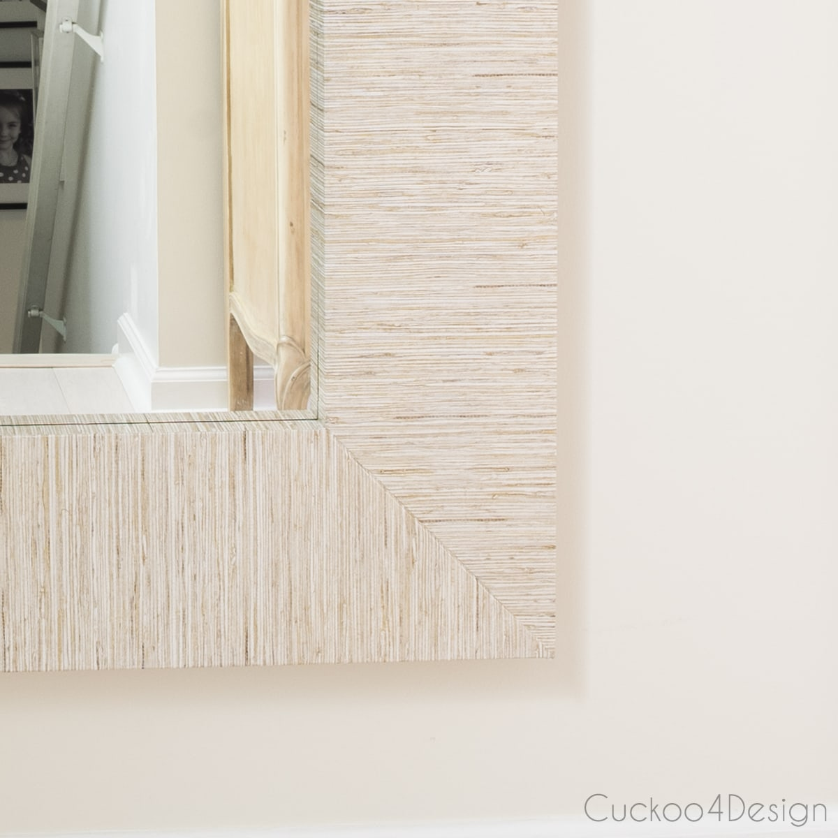 close up of Ikea Mongstad mirror with faux grasscloth wallpaper hanging on the wall