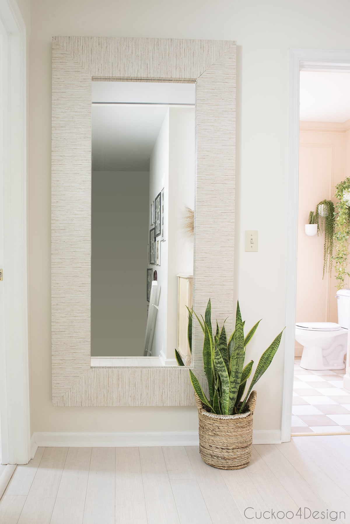 Ikea Mongstad mirror with faux grasscloth wallpaper hanging in the hallway